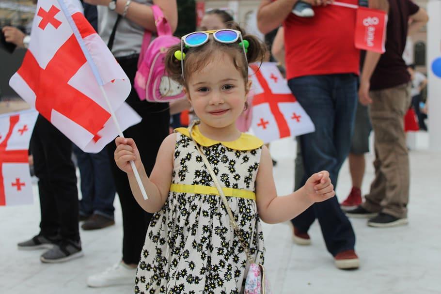 Feliz niña ondea la bandera georgiana. Cuidado: Georgia puede ser muy peligroso.